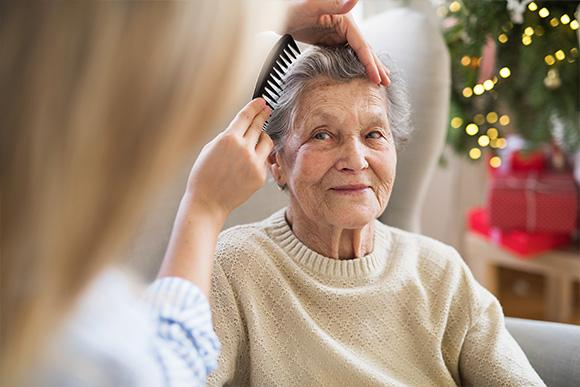 Home care in London. Domiciliary care services. Younique Care. Elderly Care. Brush elderly woman hair