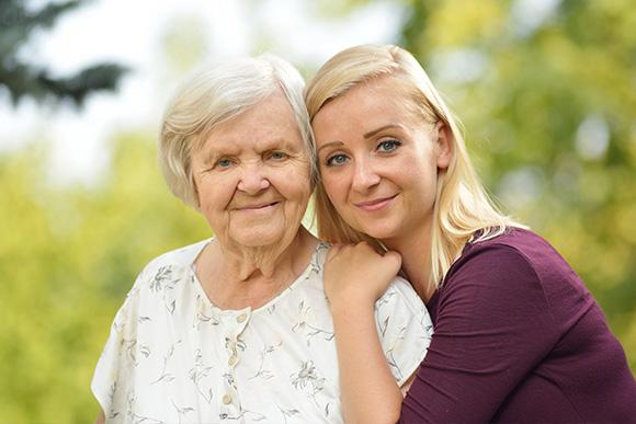 Home care in London. Domiciliary care services. Younique Care. Rehabilitation care. Young woman hugging elder